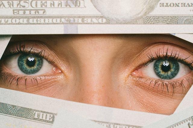 Oczy kobiety i pieniądze wokół twarzy